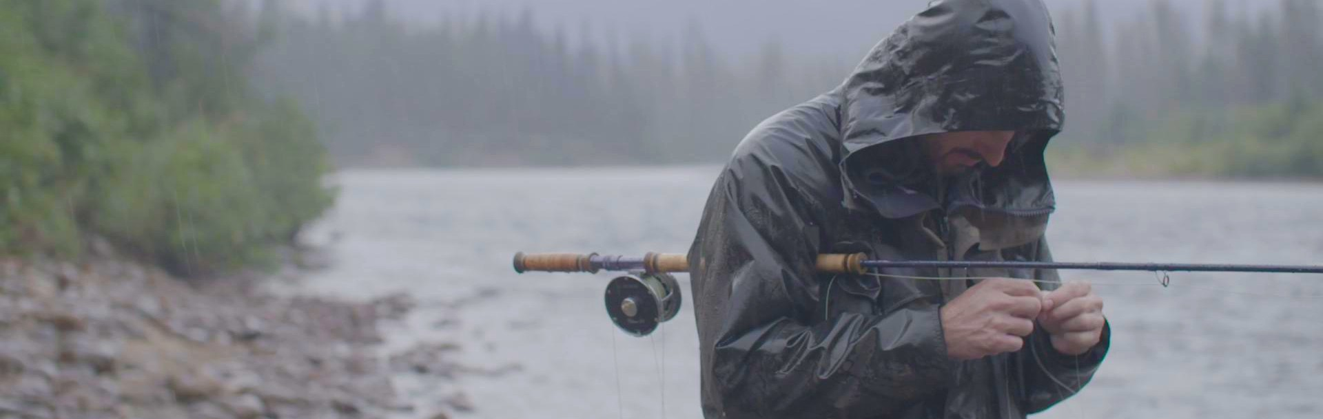 A man in the rain tying a fly to his rod